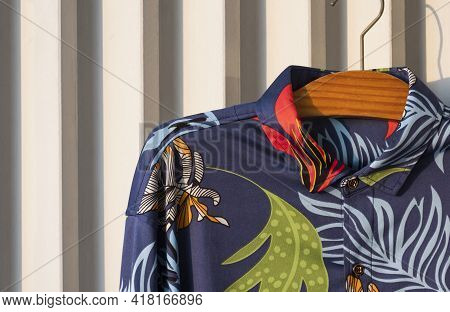 Dark Blue Hawaiian Shirt With Tropical Foliage Pattern On Hanger Hanging On White Wooden Battens Bac