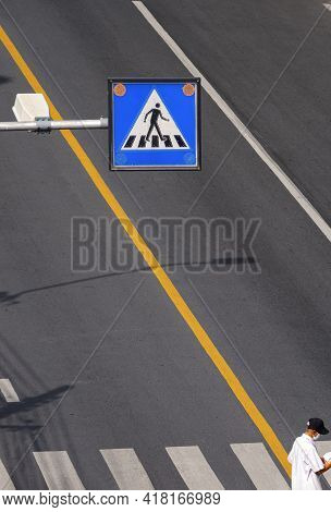 Selective Focus At Overhead Electric Pedestrian Crossing Sign With Elderly Man Is Walking On Zebra C