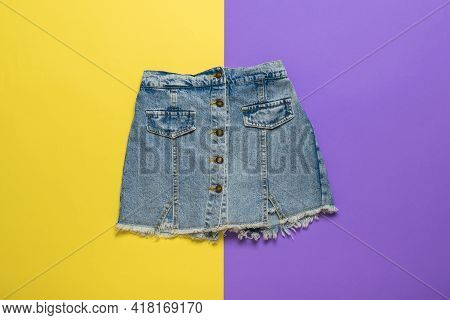 Short Denim Skirt On A Background Of Yellow And Purple Flowers. Summer Denim Clothing.