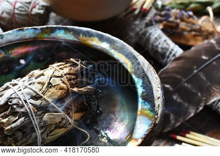 A Close Up Image Of A Smoldering White Sage Smudge Bundle And Healing Crystal On A Dark Wooden Table