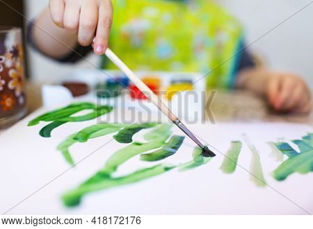Top View Of The Small Child Is Drawing With Bright Paints On Paper With Soft Effec., Close Up.
