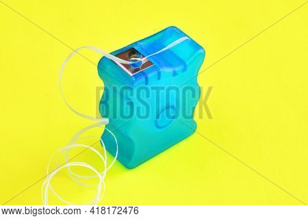 A Close Up Image Of A Blue Dental Floss Container On A Yellow Background.