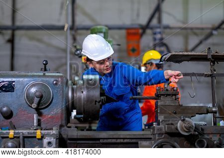 Factory Worker Woman Or Technician Look To Part Of The Machine And Inspect The Function While Her Co