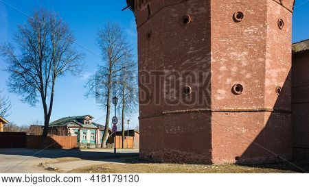 Street of Suzdal, Close up detail of red tower of Saint Euthymius monastery, residential russian small wooden traditional house across road in sunny day in spring middle april, Golden Ring of Russia