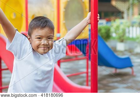 Portrait Image Of 6-7 Years Old Boy. Happy Asian Child Boy Play The Toy And Climbing The Steel Toy B
