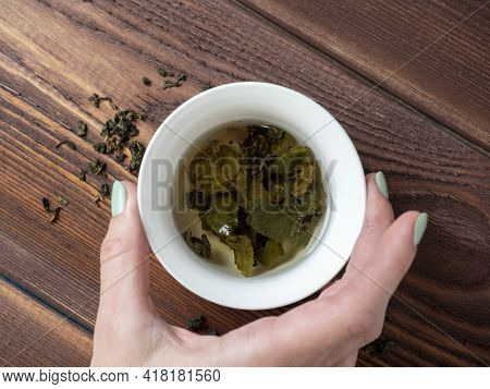 A Woman\'s Hand Holds A White Porcelain Bowl With Tea. Wooden Background. The Opened Leaves Of Large