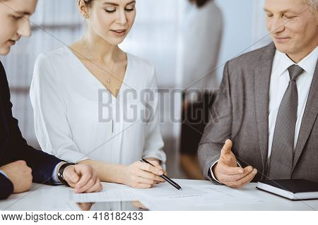 Elderly Businessman And Group Of Business People Discussing Contract In Office. Woman And Lawyers Wo