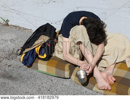 Very Poor Young Beggar While Asking For Alms From Passers-by On The Street Sidewalk Of The Metropoli