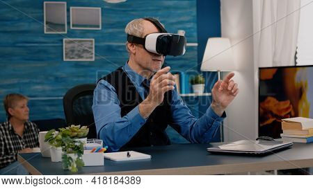 Retired Man Experiencing Virtual Reality Using Vr Headset In Living Room