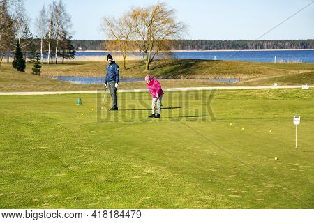 Latvia, Riga, April, 2021 - Family Playing Golf On The Banks Of The Beautiful Kisezers Lake In Riga,