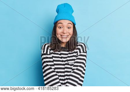 Studio Shot Of Glad Pretty Asian Woman With Dark Hair Looks Happily At Camera Dressed In Casual Stri