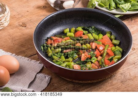 Cooking Omelet With Asparagus, Tomatoes And Spinach - Fried Asparagus, Tomatoes And Spinach In A Fry
