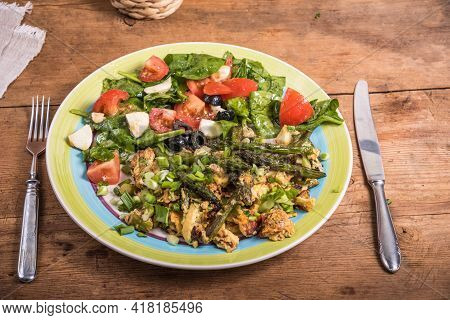 American Fried Scrambled Eggs With Asparagus, Spinach And Tomatoes In A Large Plate On A Rustic Wood