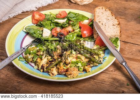 Fried Scrambled Eggs With Asparagus, Spinach And Tomatoes In A Large Plate On A Rustic Wooden Table