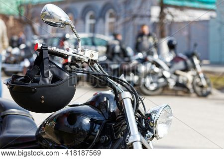 Closeup Black Moto Helmet On Motorcycle Handlebars Against Blurred Background