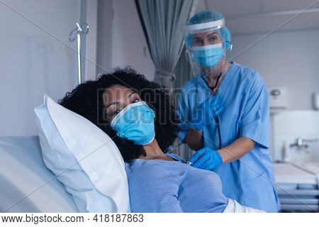 Caucasian female doctor in hospital in face mask examining female patient with stethoscope. medical professional at work during coronavirus covid 19 pandemic.