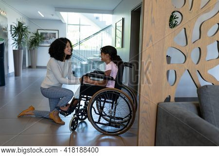 Happy mixed race mother kneeling holding hands talking with daughter in wheelchair in hospital foyer. medicine, health and healthcare services.