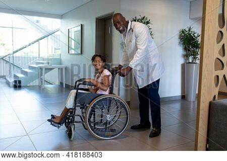 Smiling african american male doctor pushing mixed race girl in wheelchair through hospital corridor. medicine, health and healthcare services.