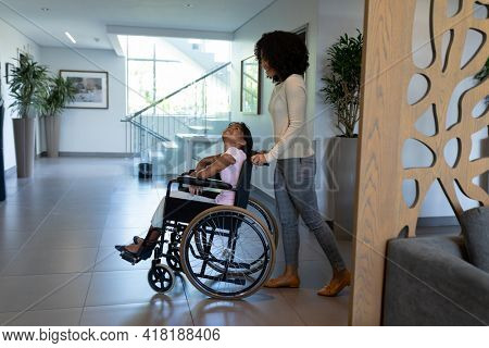 Happy mixed race mother pushing smiling daughter in wheelchair through hospital foyer. medicine, health and healthcare services.