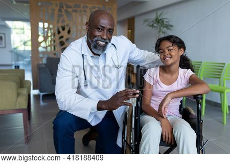 Portrait of smiling african american male doctor and mixed race girl in wheelchair in hospital foyer. medicine, health and healthcare services.