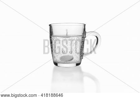 Soluble Fizzy Tablet Fallen To Transparent Glass Mug On White Background