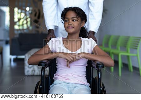 African american male doctor pushing smiling mixed race girl in wheelchair through hospital corridor. medicine, health and healthcare services.