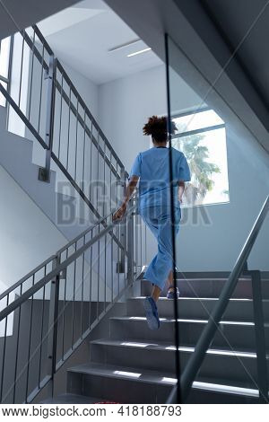 Rear view of mixed race female doctor wearing scrubs running up stairs in hospital. medical professional at work.