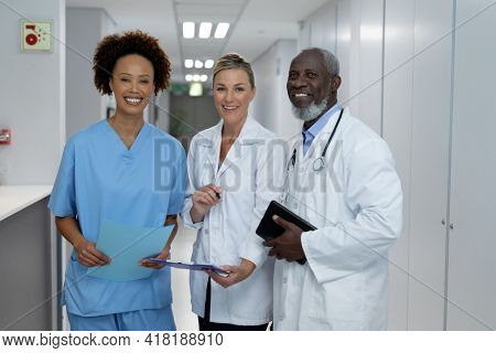 Portrait of three diverse male and female doctors standing in hospital corridor smiling to camera. medicine, health and healthcare services during coronavirus covid 19 pandemic.