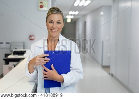 Portrait of happy caucasian female doctor standing in hospital corridor holding medical document. medicine, health and healthcare services.