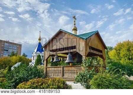 Wooden Belfry With Ancient Bells, Immersed In Greenery Of The Garden Of Kizichesky Monastery, Kazan,