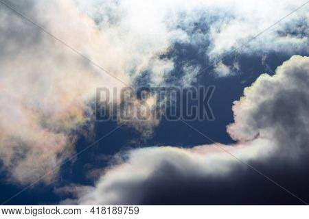 White Clouds With Iridescence Against The Blue Sky