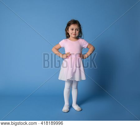 Cute Girl Ballerina Dressed In Pink Uniform Posing Into The Camera With Arms On Waist Over Blue Back