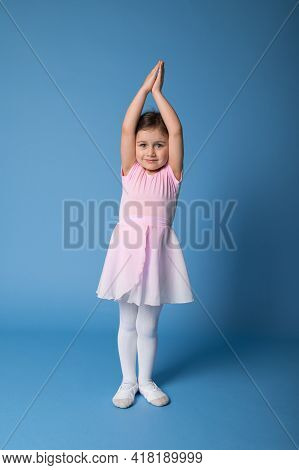 Adorable Ballerina In Pink Dress Stands On Blue Background And Raises Her Arms Up Thereby Stretching