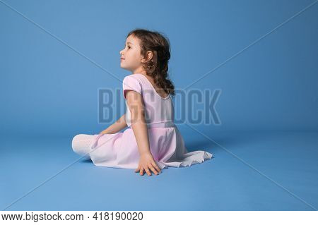 Rear View Of A Resting Preschool Girl Ballerina Dressed In Pink Uniform After Dancing, Sitting On Bl