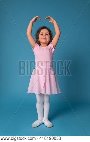 Cute Smiling Ballerina In A Pink Dress Performs A Pose In A Ballet Dance While Standing With Raised