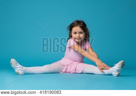 Beautiful Little Girl Ballerina In Pink Dress Sitting On A Blue Background, Practicing And Stretchin