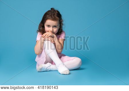 Adorable Child Ballerina In Pink Dress Looking At The Camera, Sitting On A Blue Background And Parti