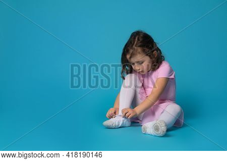 Cute Ballerina Focused On Tying Shoelaces On Ballet Shoes Sitting On Blue Background With Copy Space