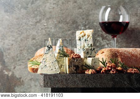 Blue Cheese And Red Wine On An Old Stone Table. Cheese With Walnuts, Bread, And Rosemary. Copy Space
