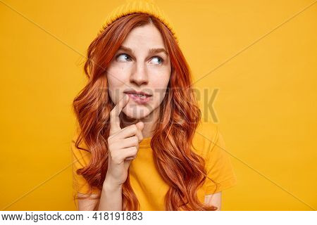 Cute Blue Eyed Ginger Female Model Keeps Finger Near Lips Tries To Make Up Her Mind Focused On Right
