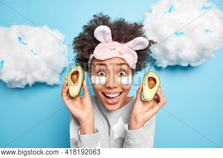 Happy Surprised Afro American Woman Holds Two Halves Of Fresh Ripe Avocado Undergoes Face Care Proce