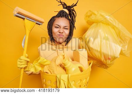 Horizontal Shot Of Busy Housewife Smirks Face Makes Grimace At Camera Holds Big Trash Bag Going To W