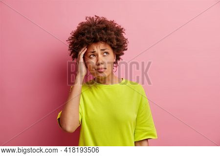 Studio Shot Of Thoughtful Puzzled Curly Haired African American Woman Keeps Hand On Head Focused Asi