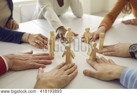 Team Of Business People Put Little Human Figures In Circle As Symbol Of Community And Teamwork
