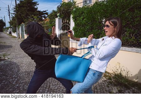Thief Or Robber In The Mask Trying To Steal Womans Bag Outdoors. Woman Using Pepper Spray Or Tear Ga