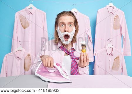 Startled Redhead Man Looks With Omg Expression At Camera Shaves And Irons Clothes Strokes Outfit For