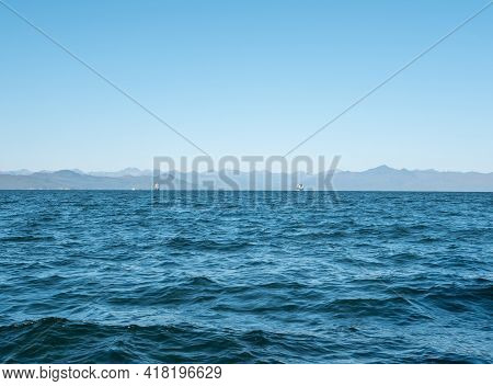 Exit On A Yacht To The Avacha Bay Of The Pacific Ocean. Large Ships On The Horizon Sail Towards The
