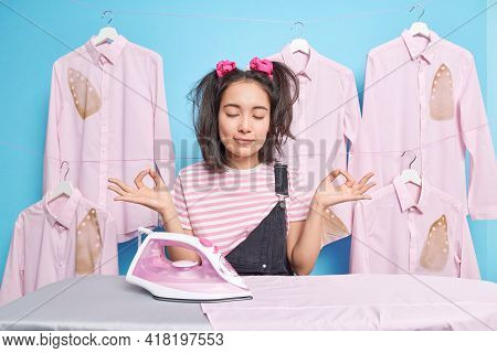 Beautiful Dark Haired Asian Woman Keeps Eyes Closed Meditates During Break After Ironing Dressed Cas
