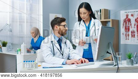 Portrait Of Multi-ethnic Doctors Speaking In Hospital Cabinet At Work Asian Young Beautiful Female P