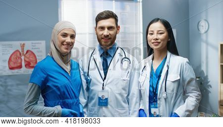 Portrait Of Happy Joyful Young Professional Physicians Standing In Hospital Looking At Camera And Sm